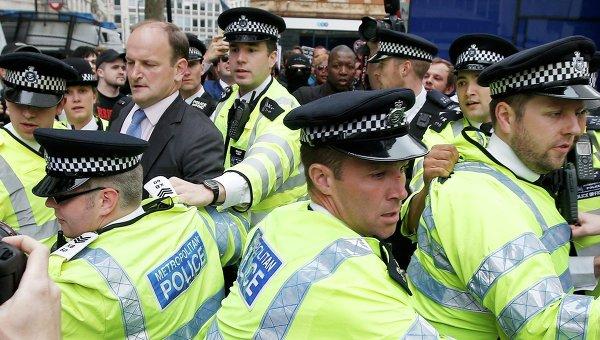 Депутат Дуглас Карсвелл, подвергшийся нападению демонстрантов, в сопровождении полиции